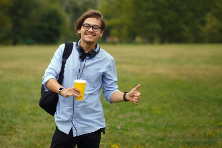 Potrait of youth student in eyeglass with backpack, holding a cup of coffe and showing thumbs up, isolated on a green park background. - Image 免版税图像