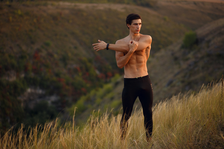 Image of a athlete, muscular, fit, abs, sportive young man shirtless doing stretching exercises with hands high, isolated on a clean sky background. Copy space.