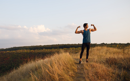 Portrait profile of a athlete, muscular, fit, abs, sportive young man doing stretching exercises with hands, isolated on a beautiful landscape background. Copy space.