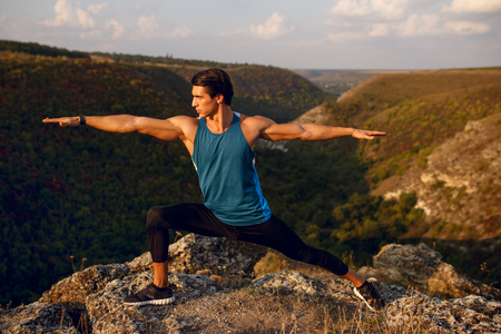 Athlete, muscular, fit, abs, young man doing stretching exercises before workout outside on forest, mountain background. Summer landscape. Copy space. Фото со стока