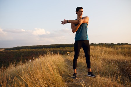 Profile of a strong, muscular, fit, sexy runner man in sportswear outside, isolated on a beautiful summer sunset landscape background. Healthy lifestyle, with copy space.