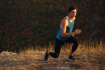 Athletic, muscular, fit, young man wearing in a sportswear, runner outside, isoalted on a sunset mountain landscape background. Фото со стока
