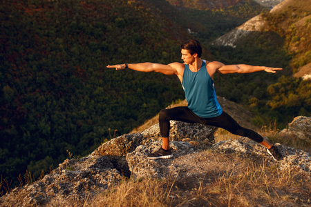 Image of a athlete, muscular, fit, abs, sportive young man doing body workout. Summer sunset landscape. Фото со стока