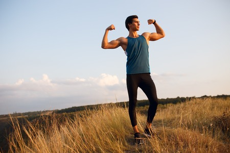 Image of a athlete, muscular, strong, fit, abs, sportive young man shows his muscles, isolated on a beautiful landscape background. Copy space.