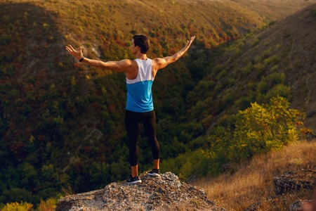 Image of a back athlete, muscular, fit, abs, sportive young man doing stretching exercises, before workout outside on forest, isolated on a mountain background. Summer sunset landscape.