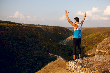 Image of a back athlete, muscular, fit, abs, sportive young man doing stretching exercises with raised hands, before workout outside on forest, isolated on a mountain background. Фото со стока