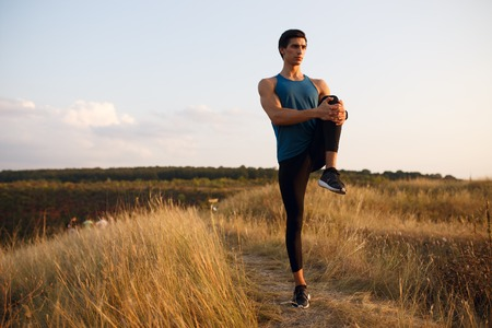 Profile of a athlete, muscular, fit, abs, sportive young man doing stretching exercises with right feet, isolated on a sunset and clouds sky background. Copy space. Фото со стока