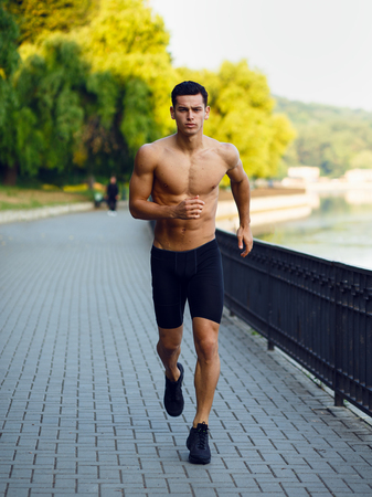 A frontal pictures of a young athletic, fit, muscular man shirtless, running morining in park, isolated on nature background. Workout lifestyle.Vertical view.