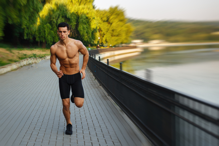 Handsome sexy male athlete young man with naked torso, Morning run in open air in urban park, early sunny summer morning. Sports lifestyle concept. Outside background. Horizontal view.