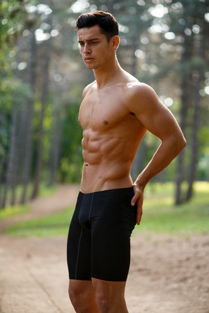 A sportsman doing workout outside with naked torso, abs, athletic, muscular body, sitting in knee, isolated on nature background. Healthy lifestyle concept. Park, summer time. Vertical view.