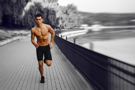 Moving, black and white image. Young athletic, fit, muscular man with naked torso, running morining in park, isolated on summer nature background. Horizontal view. Фото со стока