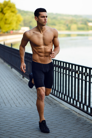 A young sportsman with naked torso running along morning in a park summer. Nature, outside background. Healthy lifestyle concept. Vertical view.