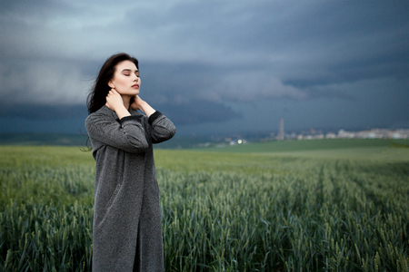 Woman touching neck with eyes closed under the cloudy sky in the field. Horizontal view. Фото со стока