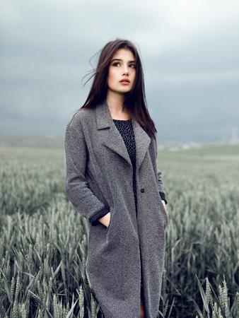 Beauty portrait a brunette girl in a grey overcoat, stand in green field, on a dark sky background.