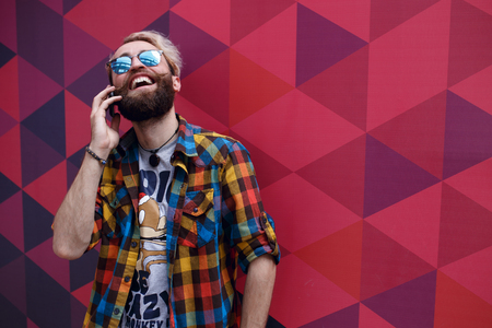 A portrait of happy smiling young bearded man in sunglasses, talking on his phone on colorful background with hexagons geometric form. Copy space. Horizontal view.