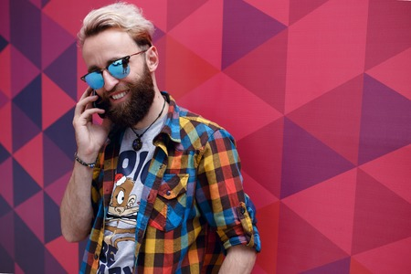 Portrait of a handsome hippster young man talking on his mobil phone, isolated on a colorful hexagons geometric form background.