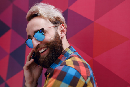 Image of a happy hipster young man in sunglasses, holding a mobile phone, isolated on a colorful background with hexagons geometric form. Copy space. Horizontal view. Фото со стока