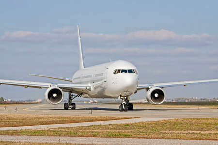 Big white passenger jet taxiing to the runway Stock Photo