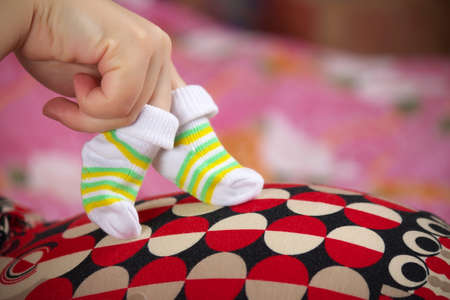 Fingers wearing baby's socks walking on the pregnant belly