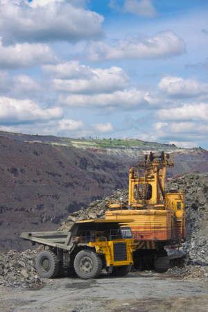 Excavator loading iron ore into the heavy dump truck on the iron ore opencast mining photo