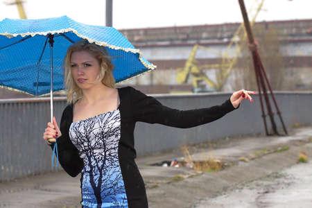 Girl with umbrella walking under the rain photo