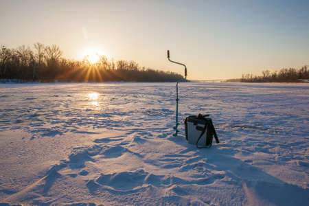 Ice fishing scene - sunrise on the river photo