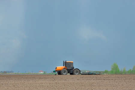 plough machine: Orange tractor cultivating the field in spring with the stormy sky on the background Stock Photo