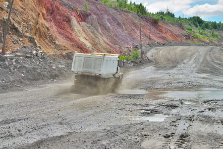 dump truck: Dump truck driving along the iron ore opencast Stock Photo