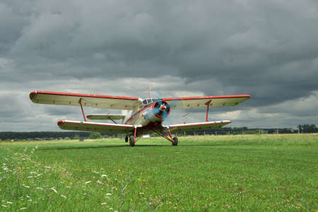 Old propeller biplane taking off from the rough airstrip with stormy clouds on the background photo