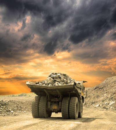 Pesado camión de volteo que lleva el mineral de hierro en la minería a cielo abierto en la puesta del sol Foto de archivo