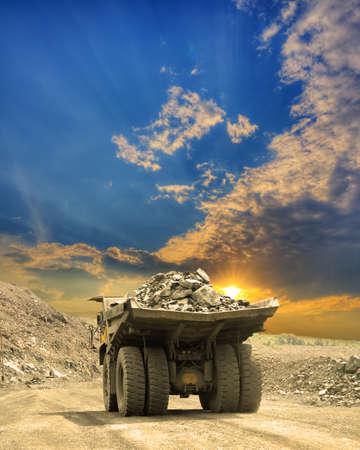 Pesado camión de volteo que lleva el mineral de hierro en la minería a cielo abierto en la puesta del sol