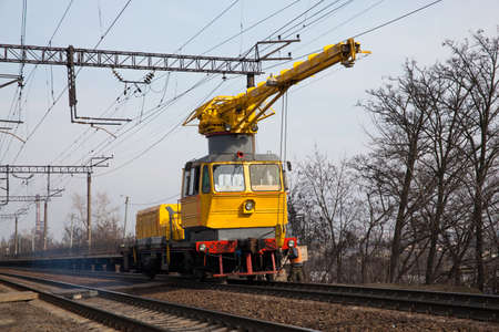 Railway service car with crane in operation repairing the track