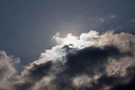 actual: Sun eclipse during the daytime with some clouds (actual image) Stock Photo