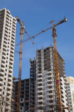 construction site: Two cranes developing residential buildings against blue sky