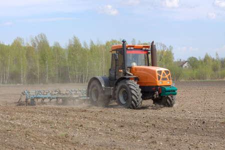 arando: Tractor con un cultivador de arar el campo en la primavera