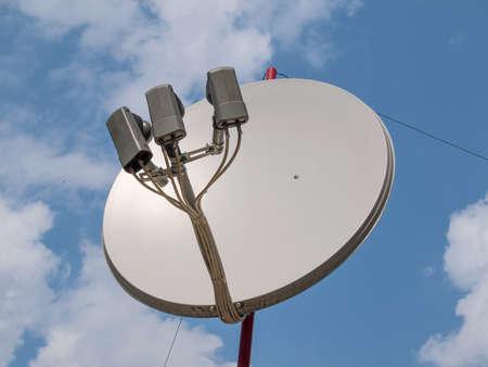 satellite tv: White satellite TV dish aerial with three heads Stock Photo