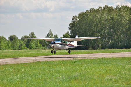 Light plane landing on the runway on the airfield Stock Photo