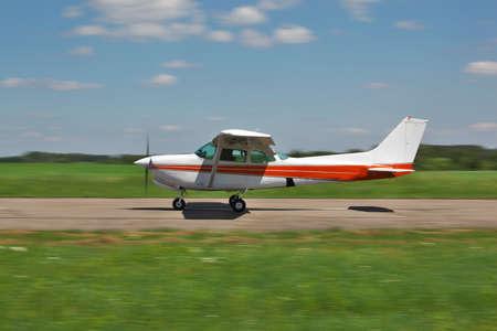 航空機: 軽飛行機の滑走路に沿って高速移動 写真素材