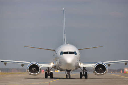 White passenger plane taxiing to the runway in the airport Stock Photo