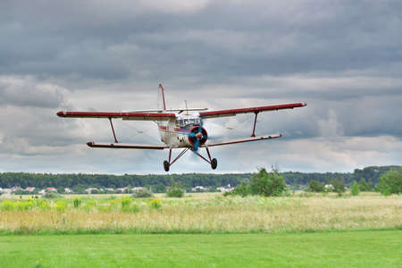airstrip: Old biplane landing on grass airstrip with stormy clouds on the background