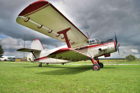 airstrip: Old biplane preparing for a takeoff from the grass airstrip with dramatic sky background