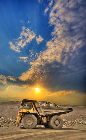 Camión minero pesado cargado con mineral de hierro en el cielo abierto con hermosa puesta de sol Foto de archivo
