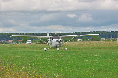 airstrip: Light private plane taking off from the ground airstrip on a stormy day Editorial