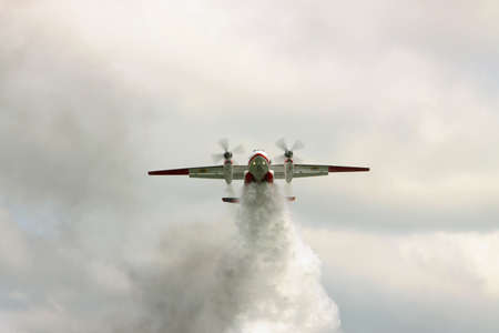 extinguish: Nezhin, Ukraine - May 5, 2010: Ukrainian Emergency Service An-32P firefighter plane is dropping a load of water to extinguish the fire in the forest
