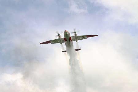 bombera: Nezhin, Ucrania - 5 de mayo de 2010: Servicio de Emergencia ucraniano An-32P avión bombero está cayendo una carga de agua para extinguir el fuego en el bosque