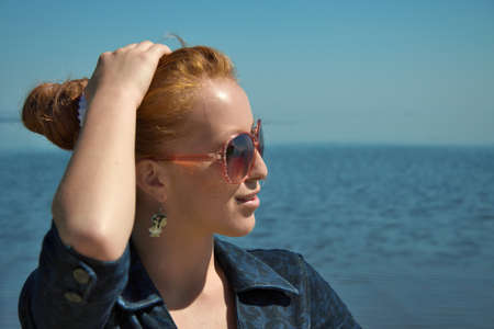 red haired girl: Portrait of a pretty red haired girl on the beach