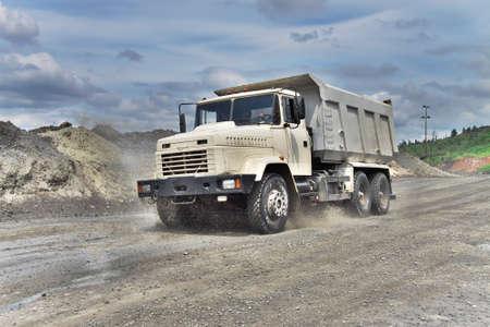 camion minero: Poltava, Ucrania - 26 de junio de 2010: Volcado de conducci�n de camiones a lo largo del camino fangoso en el mineral de hierro a cielo abierto