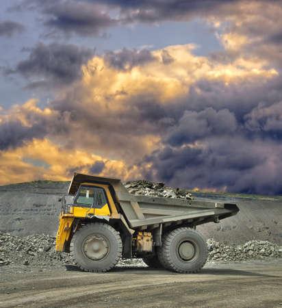 camion minero: Camión minero pesado cargado con mineral de hierro en el cielo abierto con las nubes tempestuosas