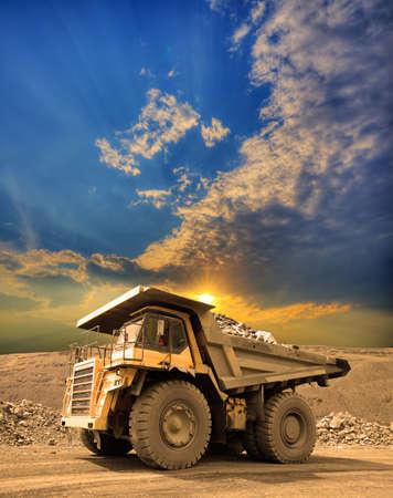 Camión minero pesado conducir por el mineral de hierro a cielo abierto en la puesta del sol