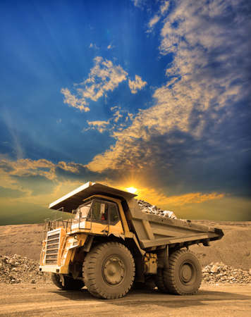 Heavy mining truck driving through the iron ore opencast on sunset